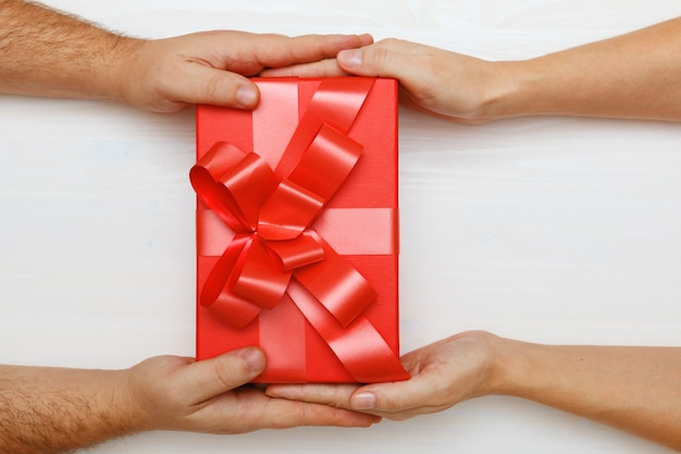 Closeup of a man's hand giving a box with a gift to a woman.