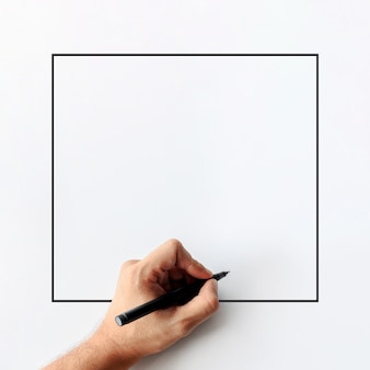 Closeup of man's hand is holding a pen showing writing gestures on a white blank background. top view