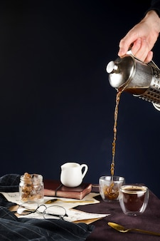 Closeup of man's hand pouring black coffee from french press into a cup on a wooden table with glasses, milk holder, cane sugar and notebook, selective focus