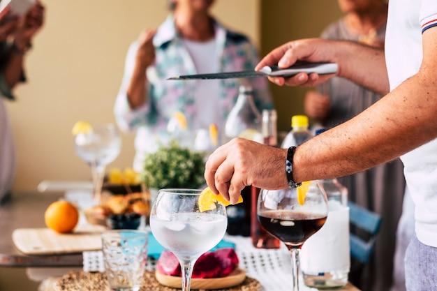 クローズアップの男性の手は、自宅の友人のためにワインとアルコールカクテルを準備します