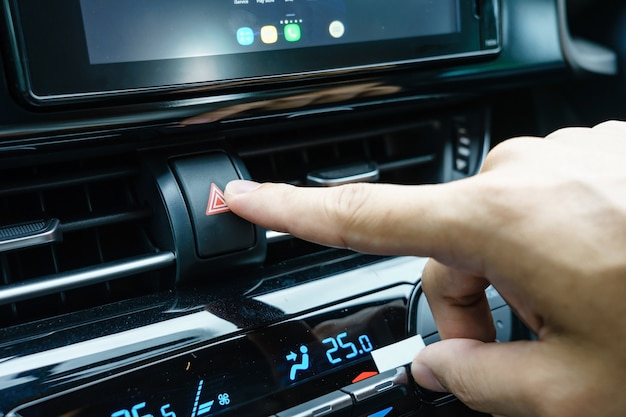 Closeup of man's hand pressing emergency stop button in car