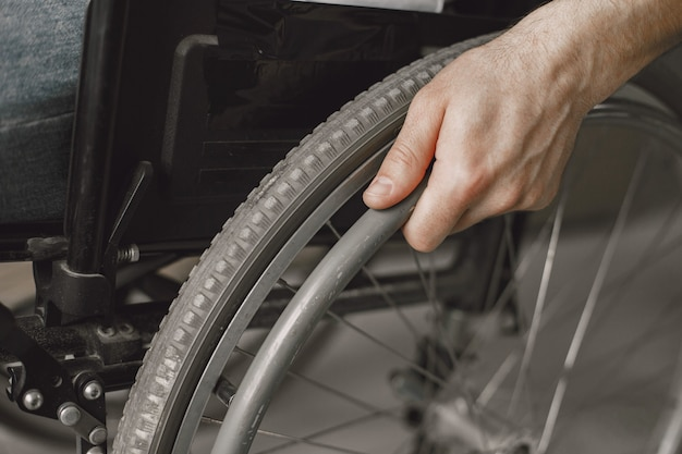 Closeup of a man's hand on the wheel of his wheelchair.
