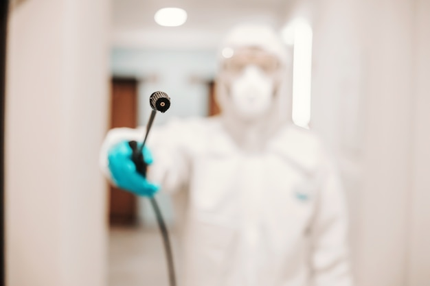 Closeup of man in sterile suit disinfecting hall of the building. protection from corona virus.