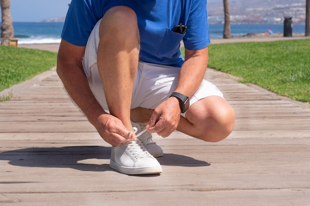 Closeup of man tying shoe laces. male sport fitness runner getting ready for jogging outdoors in spring or summer.