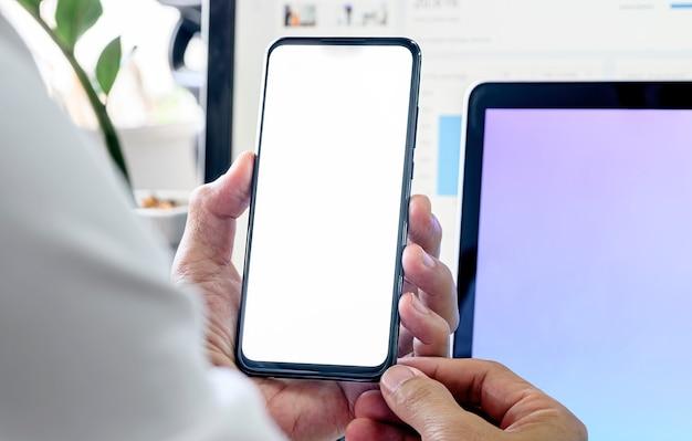 Человек крупного плана используя smartphone с пустым экраном пока сидящ на столе офиса.