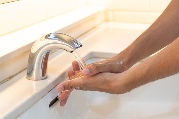 Closeup man washing hands with soap under the faucet with water in the bathroom.