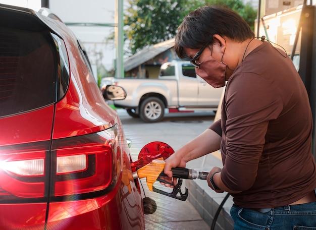 직물 보호용 안면 마스크를 쓴 클로우즈업 남자는 빨간 차에 휘발유를 급유하는 가스 펌프 도구 손잡이를 잡고, 주유소 작업