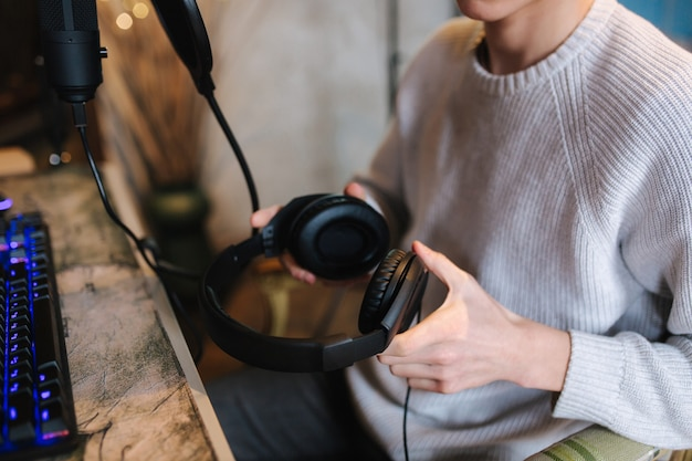 Closeup of man wearing headphones during the work with music at home