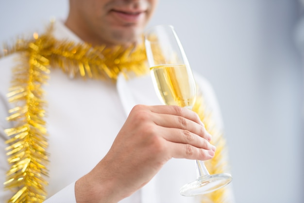 Closeup of man wearing tinsel and drinking champagne