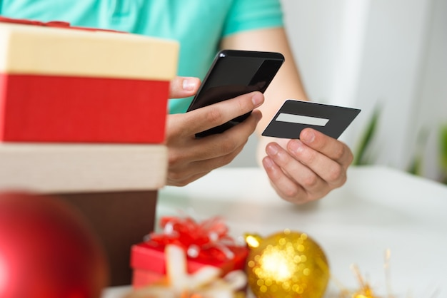 Closeup of man with credit card, smartphone and christmas gifts