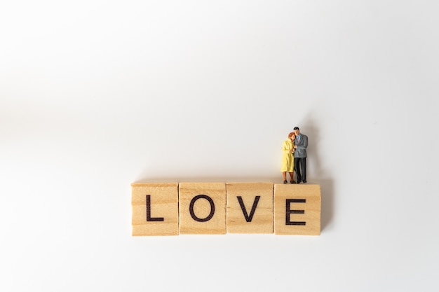 Closeup of man and woman miniature figure people standing on wooden letter block wording love on white.