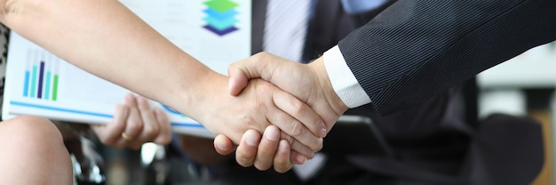 Closeup of man and woman shaking hands in front of smiling man with documents. conducting business deals concept.
