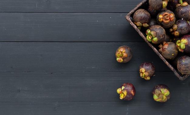 Closeup mangosteen fruit on black wood