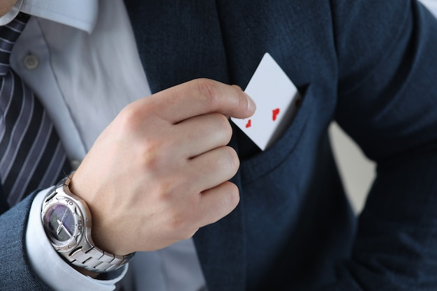 Closeup of mans hand pulling ace card out of suit pocket