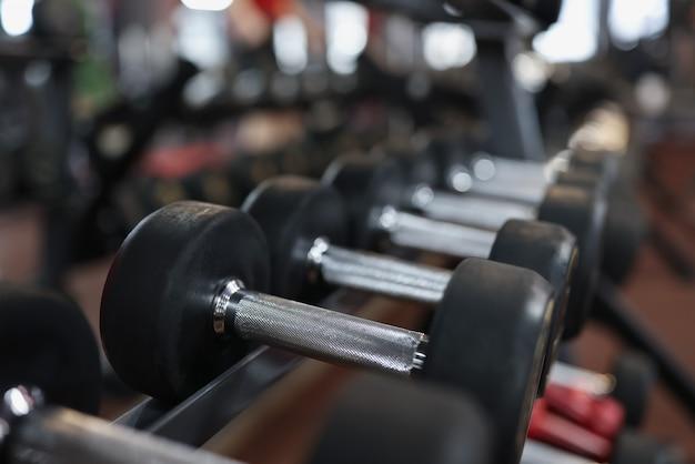 Closeup of many black dumbbells on rack in gym body shaping through regular sports training