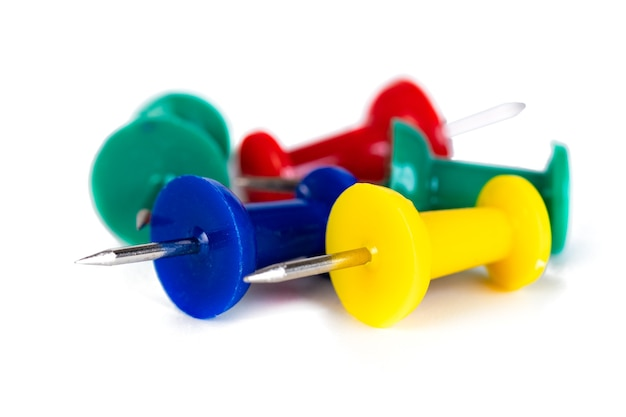 Closeup of many colored thumbtacks on white, stationery