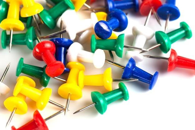 Closeup of many colored thumbtacks on white.