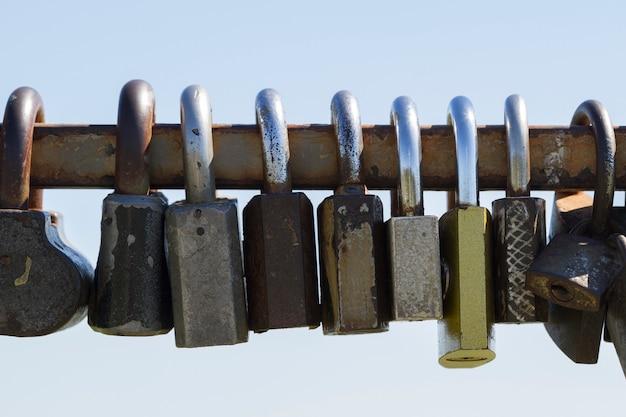 Closeup of many love locks on iron fence.