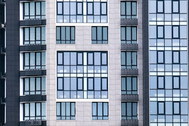 Closeup of many windows on a gray facade of modern apartment building. for real estate background.