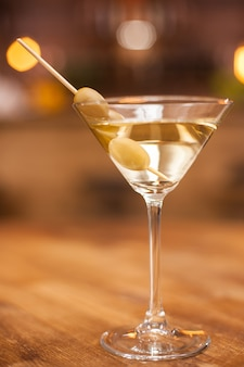 Closeup of a martini glass with olives on a wooden table in a resturant. fresh drink. tasty drink. alcoholic drink.