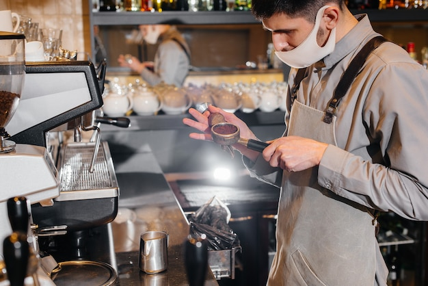 Closeup of a masked barista preparing a delicious coffee at the bar in a cafe