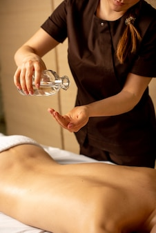 Closeup of masseur hands pouring aroma oil on woman's back