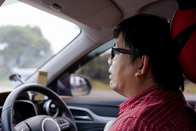 座って車を運転中にストレスや恐怖や悲しい表情でクローズアップ成熟したアジア人。携帯電話のgpsナビゲーター。損失を得る。悪い旅の眼鏡男