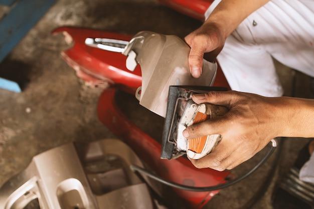 クローズアップメカニックワーカー研磨バイクのボディを研磨し、駅のサービスで塗装の準備