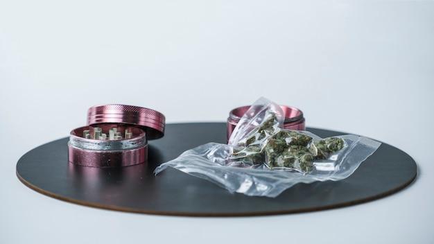 Closeup of medical marijuana buds in vacuum seal bags and grinder