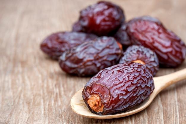 クローズアップmedjool日付またはテーブルの上の木のスプーンの日付フルーツ