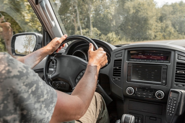 Closeup of men hands holding steering wheel and driving in nature road trip of man inside auto durin...