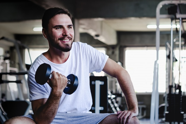 Closeup men healthy holding dumbbell workout and building body at gym fitness