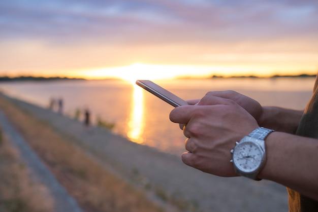 Closeup men using smartphone at sunset
