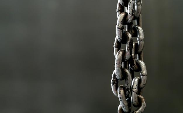 Closeup metal chain on old drick wall