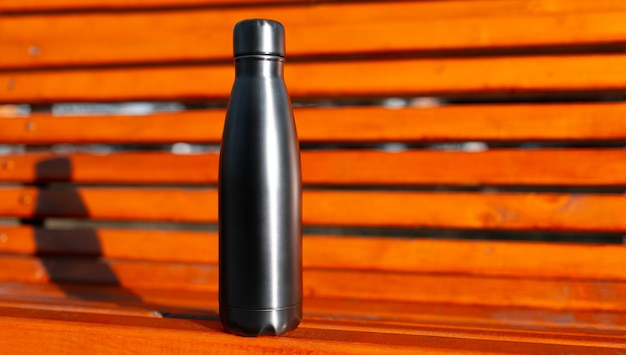 Closeup of metal thermo water bottle of black on background of orange wooden bench with copy space. reusable bottles zero waste eco concept.