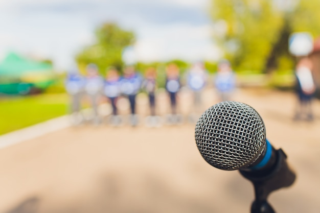 Closeup microphone in blurred background with effect film bright light filter, single microphone in the park and blurred background.