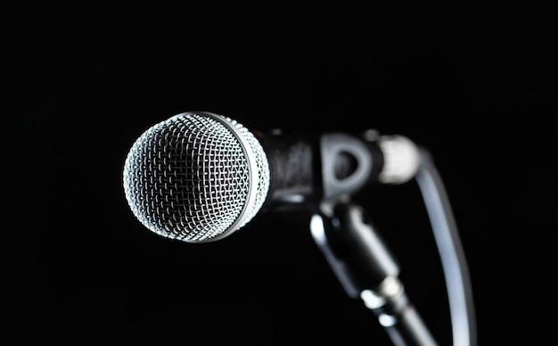 Микрофон крупного плана. вокальный аудиомикрофон на черном фоне. живая музыка, аудиотехника. концерт караоке, поют звук.