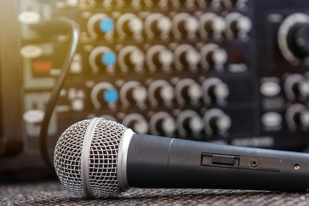 Closeup microphone with blurred sound mixer background.