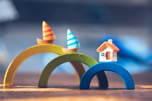 Closeup miniature house with miniature sailboat on colorful wooden block using as property and family concept