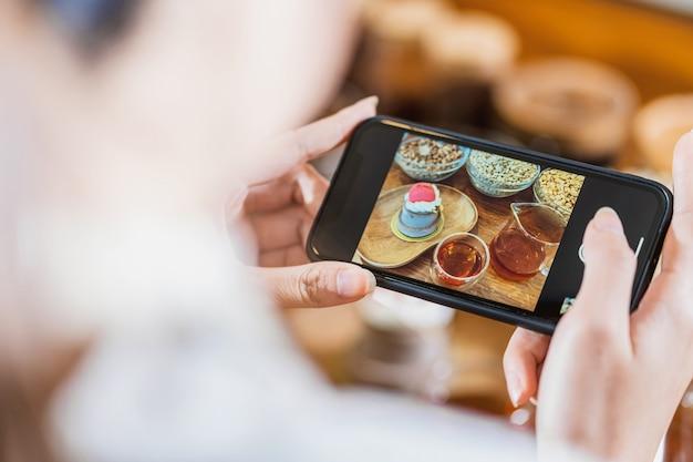 コーヒーの水差しを添えて蜂蜜とカップケーキベーカリーの写真を撮るクローズアップ携帯電話