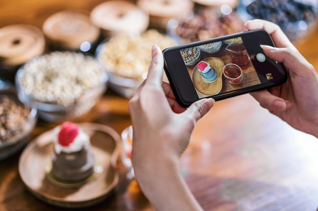 Мобильный телефон крупным планом фотографирует пекарню кексов с медом и кофе