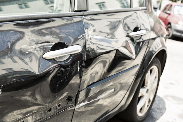 Closeup of modern black car with dents