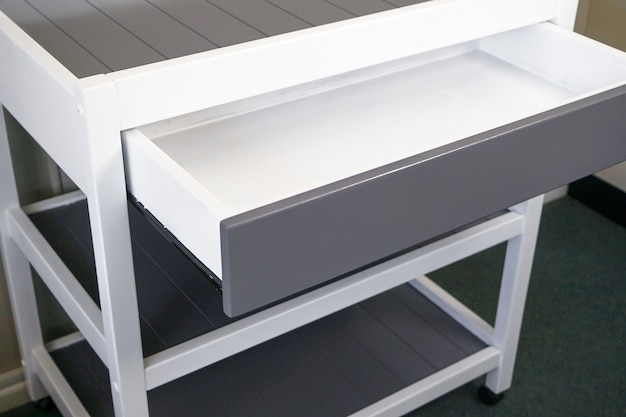 Closeup of a modern white table with a drawer under the lights