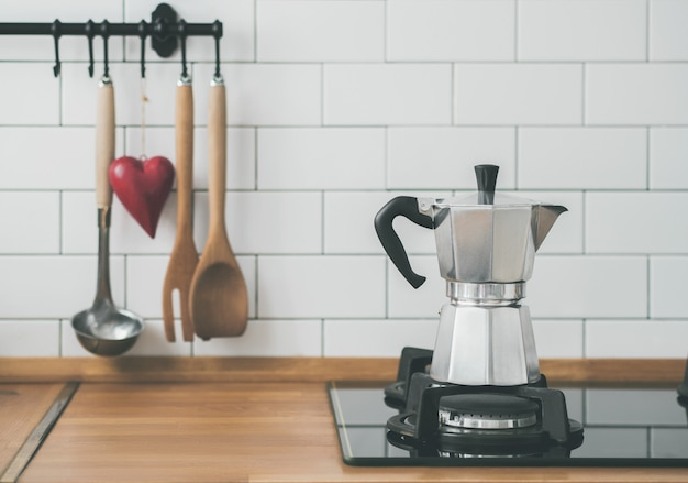 Closeup of moka coffee pot on a gas stove against a wall with white tiles in kitchen