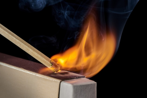 Closeup of the moment when the match ignites when moving along the box