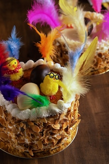 Closeup of a mona de pascua, a cake eaten in spain on easter monday, ornamented with feathers.