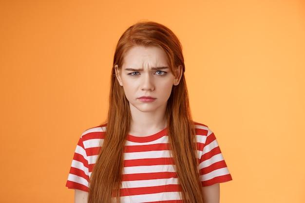 クローズアップ不機嫌そうな子供っぽい赤毛の女の子が不公平な状況を嫌悪し、眉をひそめている不満を訴えている...