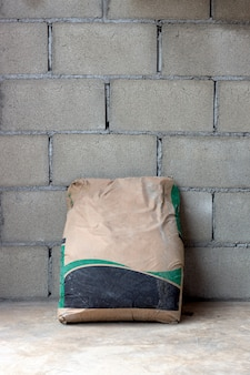 Closeup mortar sack on brick wall in construction site workspace