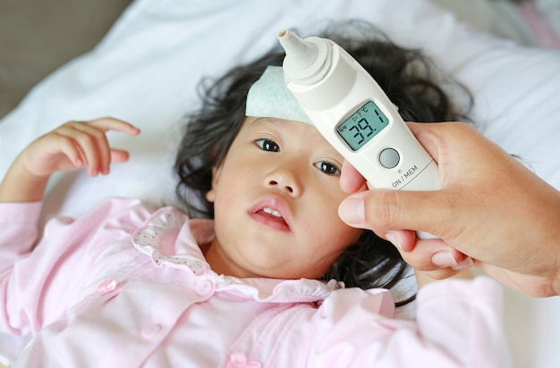 Closeup mother hand takes temperature for her daughter with ear thermometer on bed