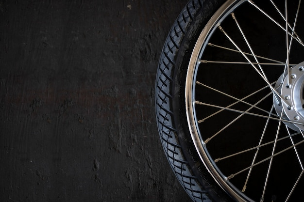Closeup motorcycle tire on old black wood background. top view. flat lay